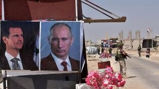 Russian and Syrian troops stand guard near posters of Syrian President Bashar al-Assad and Russia's Vladimir Putin at the Abu Duhur crossing on the eastern edge of Idlib province