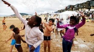 Crianças brincam na praia de Cabourg, no norte da França, 22 de agosto de 2018