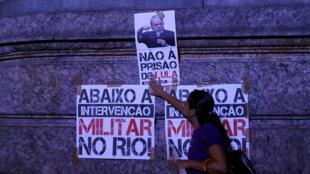 Militante cola cartaz contra a prisão de Lula em rua do Rio de Janeiro.