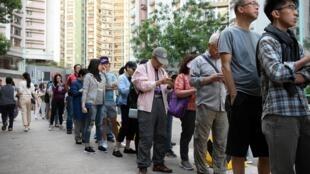 香港民众周日排队等候参加区议会选举投票资料图片