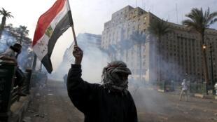Manifestante agita bandeira egípcia no momento em que polícia lança gás lacrimogêneo.