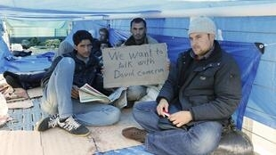 Syrian refugees occupying the walkway at Calais demand to see British PM David Cameron
