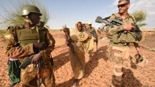 Collaboration entre un soldat malien et un militaire français engagé dans l'opération Barkhane.