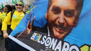 Eleitor exibe cartaz com o rosto do candidato do PSL à presidência, Jair Bolsonaro, em 21 de outubro de 2018