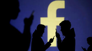 Silhouettes of mobile users are seen next to a screen projection of Facebook logo in this picture illustration taken March 28, 2018.