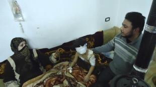 Familía síria acompanha garota ferida durante os ataques do governo em Homs, nesta segunda-feira.