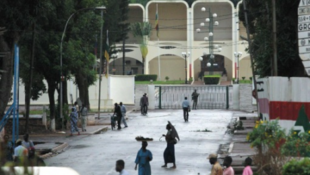 Residents of Bangui walk near the presidential palace.