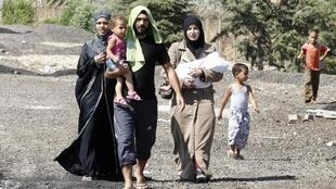 """Syrian refugees flee from a refugee camp named """"Container City"""" on the Turkish-Syrian border in Oncupinar, 22 July, 2012"""