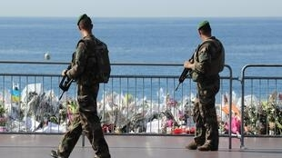 Soldiers pass by the new makeshift memorial in tribute to the victims of the deadly Bastille Day attack at the Promenade des Anglais on July 19, 2016 in Nice, after it was moved from the pavement to the seafront so that the street can be re-opened.