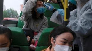 香港边境小镇发现新的冠状病毒后,一名戴着口罩和雨衣的居民自愿对乘客进行体温监测 2020年2月4日
