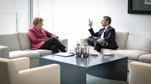 German Chancellor Angela Merkel (L) with Nicolas Sarkozy at the chancellery in Berlin on Friday