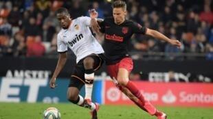 Le milieu de Valence Geoffrey Kondogbia (g) à la lutte avec le milieu de l'Atlético Madrid Marcos Llorente, le 14 février 2020 à Valence