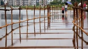 Residents walk across a bridge covered with water in the flooded area of Poyang, Jiangxi province, on 21 July 2010