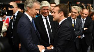 Emmanuel Macron (à direita) cumprimenta o empresário Bernard Arnault, do grupo LVMH, o homem mais rico da França.