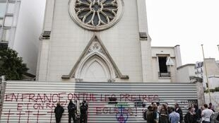 """Members of a private security agency stand in front of a barrier with an inscription which translates as """"In France, priests are killed and churchs are demolished"""" as they block the access to the Sainte-Rita church in Paris on August 3, 2016 following the"""