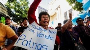 Une Guatémaltèque manifeste contre l'accord migratoire avec Washington, avec une pancarte où l'on peut lire «Président hypocrite, vend sa patrie», dans la ville du Guatemala, le 27 juilet 2019.