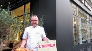 Baker Francois Brault in front of his bakery with a slab of butter and some of his creations.
