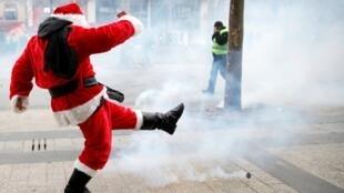 Um homem vestido de Papai Noel chuta uma granada de gás lacrimogênio em direção à polícia, na avenida Champs-Élysées, em Paris.