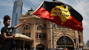"""A protester waves a flag during an """"Invasion Day"""" rally on Australia Day in Melbourne on January 26, 2018. Tens of thousands of people marched across Australia on January 26 in an """"Invasion Day"""" protest calling for a rethink of the national day they say is"""