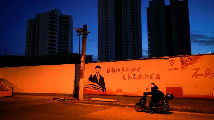 上海,戴口罩的摩托手从习近平巨幅画像前穿过。