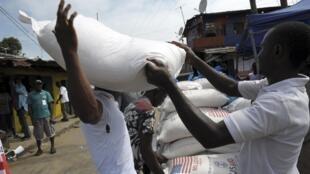 Moradores do bairro West Point de Monróvia, que foram colocados em quarentena, recebem alimentos do PAM.