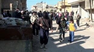 Capture d'écran d'une vidéo montrant une manifestation d'opposants au régime syrien avec des membres de l'Armée syrienne libre (ASL), à Rastane, le 28 janvier 2012.