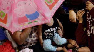 À San Pedro Sula, au Honduras, une famille attend de prendre la route, direction les États-Unis, le 14 janvier 2019.