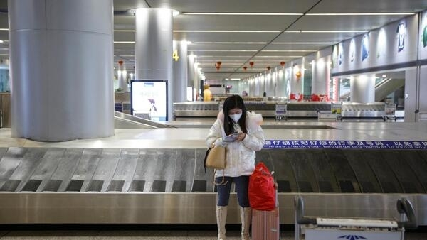A woman wearing a face mask stands in the empty luggage collection hall at the airport in Changsha, some 300 kilometres from Wuhan, as the country responds to an outbreak of a new coronavirus, 27 January 2020.