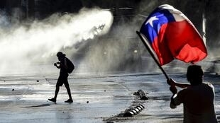 Manifestant brandissant un drapeau chilien alors que la police utilise des canons à eau, le 20 décembre.