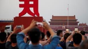 Les gens prennent des photos sur la place Tiananmen à la veille du défilé marquant le 70e anniversaire de la fondation de la République populaire de Chine à Pékin, le 30 septembre 2019.