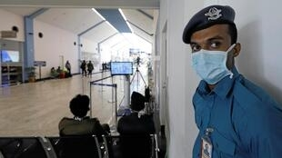 A security official wears a mask as he stands guard near a thermal scanner at Bandaranaike International Airport after Sri Lanka confirmed the first case of coronavirus in the country, in Katunayake, Sri Lanka, 30 January, 2020.