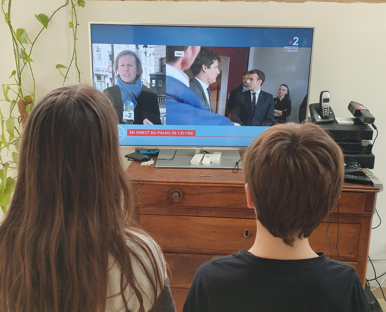 Os gêmeos Fanny e Dorian assistem as notícias com os pais. Em caso de dúvidas, é só perguntar.