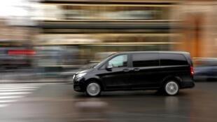 Un chauffeur Uber conduit son van dans une rue parisienne.