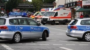 Полицейские автомобили и служба скорой помощи на месте нападения на супермаркет в Гамбурге 28 июля 2017 г.