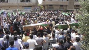 Sírios carregam caixões contendo corpos de civis assassinados pelas forças do regime de Bashar el-Assad, nesta terça-feira, em Deraa.
