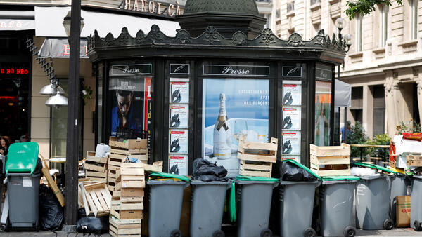 Rubbish bins around a Parisian kiosk selling newspapers and magazines, June 2016.