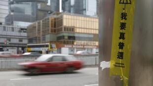 """香港警方在金鐘佔領區清場後,各大街道恢復通車,但""""我要真普選""""的標語仍然零星可見。圖片攝於2014年12月12日特區政府建築附近。"""