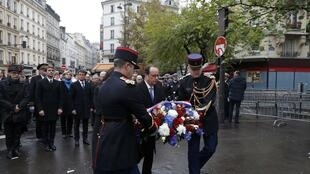 French President Francois Hollande and Paris Mayor Anne Hidalgo lay a wreath of flowers as they unveil a commemorative plaque in Paris on November 13, 2016, during a ceremony held for the victims of last year's Paris attacks.