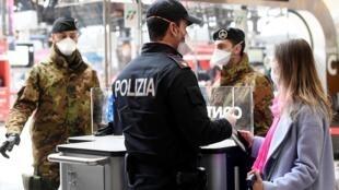 Des policiers contrôlent des personnes à la gare centrale de Milan, le 9 mars 2020.