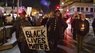 Apesar do frio e da neve, manifestantes revoltados com a discriminação policial contra os afroamericanos continuam nas ruas de Ferguson.
