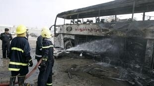 Firefighters hose down a bus whichwas targeted in the Najaf attack