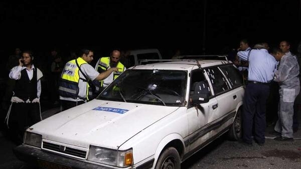 Israeli rescue service members (L) and police are seen near the vehicle which was carrying four Israelis killed in a shooting attack near a West Bank Jewish settlement, August 31, 2010.