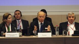 O chanceler francês, Laurent Fabius (ao centro), discursa durante reunião com opositores sírios.