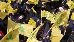 Des femmes brandissent des drapeaux du Hezbollah et du Liban, pendant le discours télévisé d'Hassan Nasrallah, le 24 mai 2015.