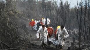 Membros da equipe de resgate carregam corpo de bombeiro morto durante o incêndio perto da cidade de Temuco, nesta quinta-feira.