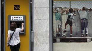 Mulher retira dinheiro em caixa eletrônico do banco Piraeus, nesta sexta-feira (19), em Atenas.