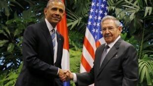 Barack Obama (g) et Raul Castro ont échangé une longue poignée de main au Palais de la Révolution de La Havane, le 21 mars 2016.