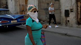 Following requests in recent weeks, communist Cuba has sent medical teams to Italy, Venezuela, Nicaragua, Grenada, Suriname, Jamaica and Belize; pictured is a woman taking precautions against the spread of COVID-19, in Havana, on March 24, 2020