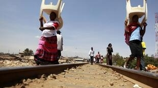 Women walk along the Kenya-Uganda railway line near Kibera slum, home to over 1 million people in Kenya's capital Nairobi