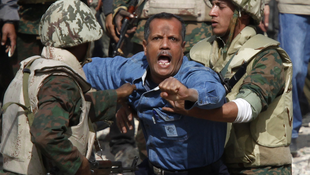 Two soldiers stop a pro-Mubarak protester from crossing Tahrir square